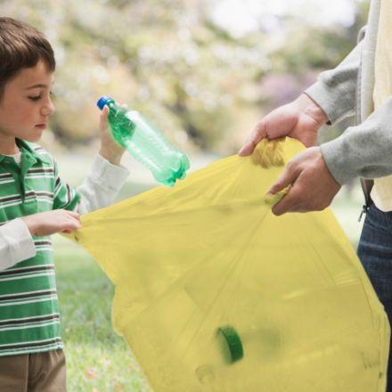Bambino ricicla rifiuti con sacco giallo
